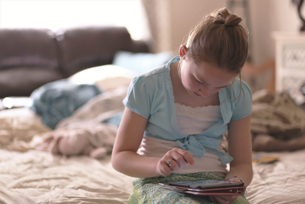 girl sitting on bed with tablet